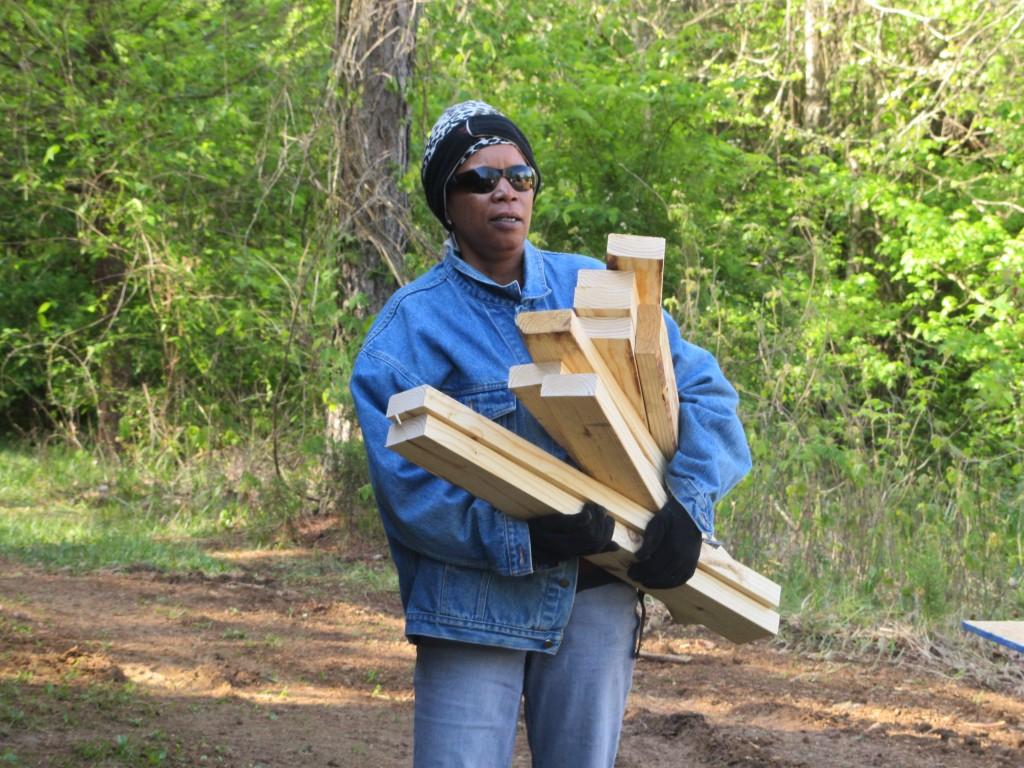 Sherwood Forest Camp Trades Weekend - volunteer carrying wood