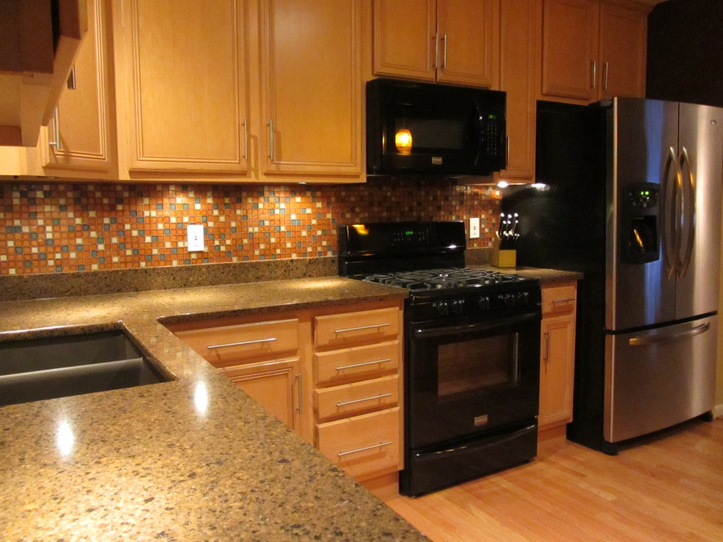 Under cabinet lighting with granite and glass tile backsplash